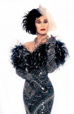 Glenn Close caracterizada como Cruella, veste um vestido de gala com uma textura de pele de cobra