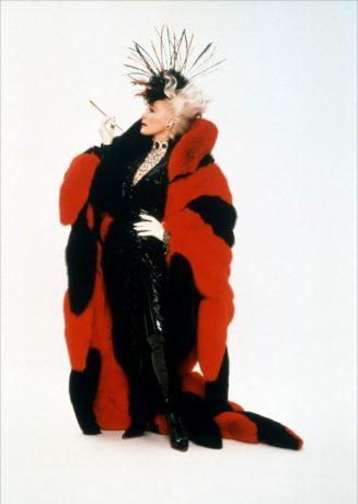 Glenn Close caracterizada como Cruella, veste um figurino preto e vermelho.