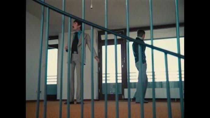 Fox e Eugen são enquadrados em um contra-plongée, no primeiro plano há um corrimão entre a câmera e os personagens.