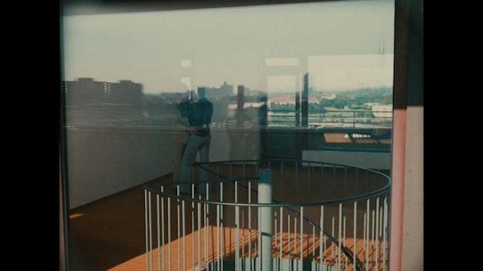 Cena de O Direito do Mais Forte é a Liberdade, onde dois personagens são visto através de uma janela, há um reflexo no vidro que não nos permite ver direito quem eles são.
