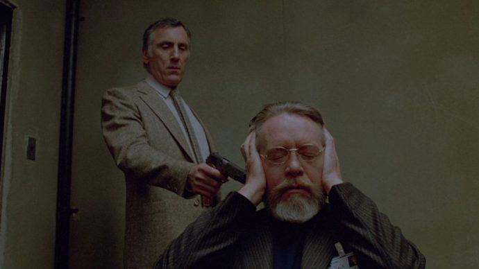 Cena de Scanners em que dr. Paul Ruth de olhos fechados e com as mãos tapando os ouvidos tenta controlar seus pensamentos, atrás dele Braedon Keller aponta uma arma em direção dele