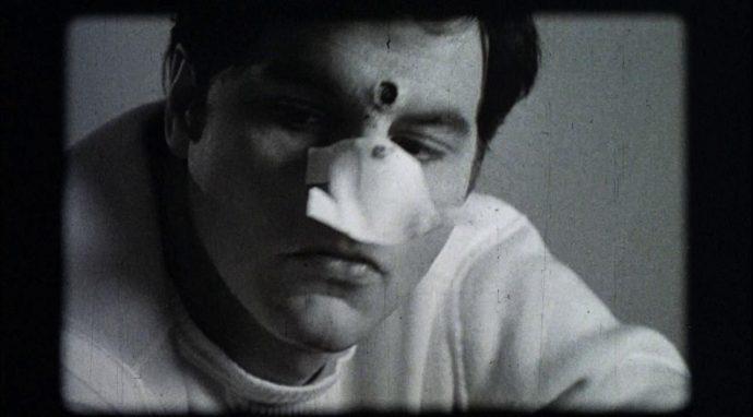 Darryl Revok, vilão de Scanners, em um vídeo antigo em preto e branco. Em sua testa há uma grande ferida.