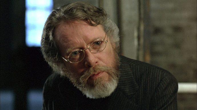 Cena de Scanners em que o ator Patrick McGoohan olha para alguém fora de quadro, o fundo está desfocada.