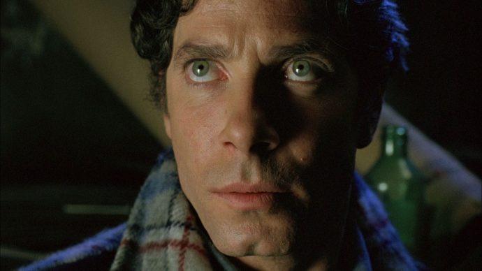 Stephen Lack, em uma cena de Scanners. Ele olha muito sério para alguém ou algo fora de quadro.