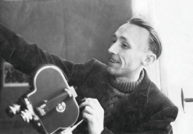 Foto do de um dos críticos mais importantes da história do cinema, o francês André Bazin. Na imagem o crítico sorri, segura uma câmera portátil e tem o braço esticado para fora do enquadramento.